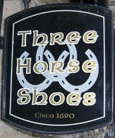 The Three Horseshoes traditional old pub sign with an interlinking horseshoes design